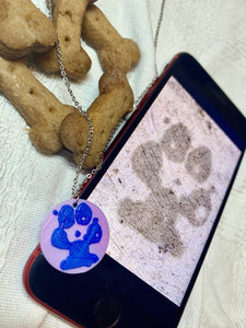Shown laying on a white fabric is a phone, a necklace with a 3D pritned pendant, and two dog bone shaped treats. The pendant is a 1 inch light purple circle with a blue paw print on it. The picture on the phone is of the same paw print and was used to create the custom print.