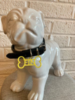Load image into Gallery viewer, In front of a white brick wall and on a grey cushion is a ceramic bulldog statue. It is wearing a black collar and has a yellow dog tag. The dog tag is 3D printed in the shape of a dog bone with the name FIN in the middle. The name can be personalized to any name you would like.