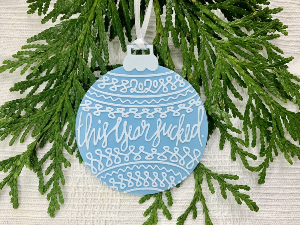 "On a white fabric background there are sprigs of everygreen and a R+D 3D printed ornament. The ornament is shaped like a traditional bulb. It is light blue with white drawings and script on it. Worked into the doodles are the year 2020 and then the words, ""this year sucked""."