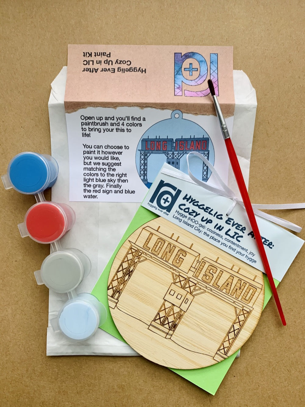 Shown laying on craft paper is the packaging and contents of this DIY Paint Kit. There is a paper envelope with instructions, a paintbrush, a set of 4 paint wells and a wall hanging with a laser cut NYC landmark.