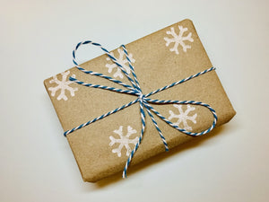 In the center of the photo is a wrapped gift. The wrapping paper is 100% recycled craft paper with white snowflakes stamped on. There is blue and white striped twine tied around the box and in a bow.