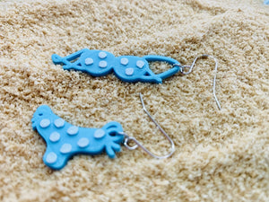 There is a pile of fluffy sand. There are two earrings in the center. They are asymmetrical earrings one is a bikini top the other is a bikini bottom. They are both teal with white polka dots.