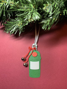 Shown on a red background hanging from a wreath is a 3D printed R+D ornament. It is in the shape of a gin bottle: green with a white label and a red emblem. Tied around the neck is a red bow that has two jingle bells attached. The entire ornament is covered in glitter to give it a shimmer and shine.