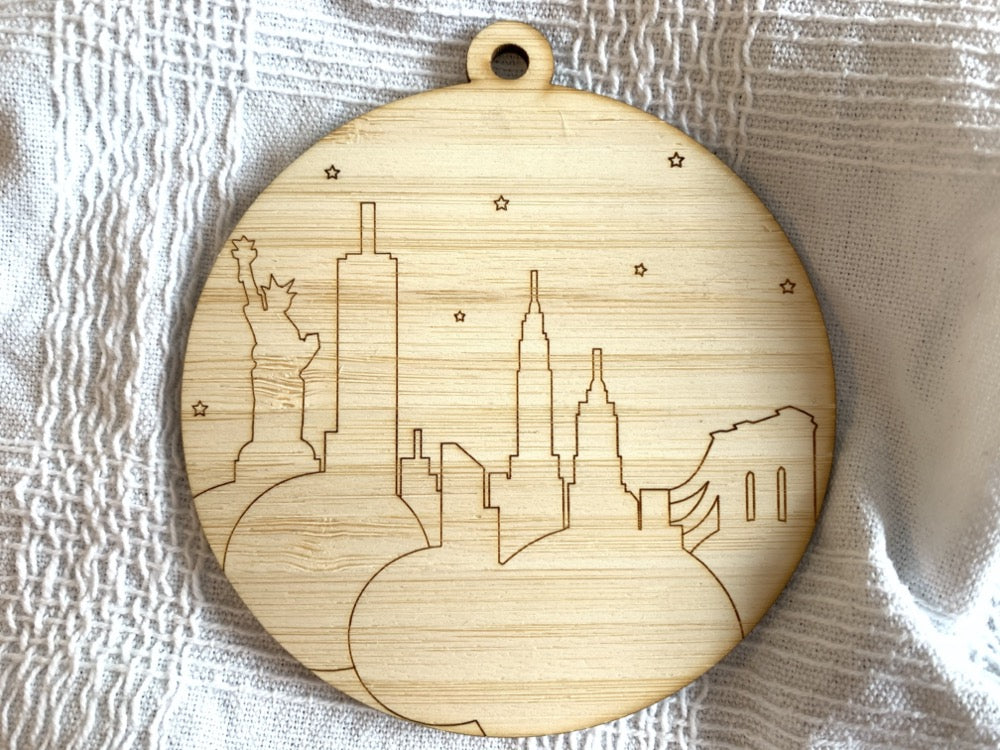 Shown on a white fabric background is a laser cut wall hanging. It is cut from bamboo, a fast growing and sustainable grass. Etched in it a picture of the New York City Skyline with the Statue of Liberty, Empire State Building, Chrysler Building and Brooklyn Bridge all visible. Each piece can be painted like a paint by number or left plain. It can hang from your Christmas Tree or on you wall all year round.