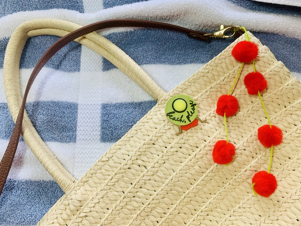 Pinned to a light straw bag is a R+D pin. It shows someone in a red bathing suit resting back on their hands. They are wearing a large brimmed yellow hat that has beach please written on it in a black script. Hanging off the bag are bright red pom poms. This is all  resting on a blue and white striped towel.