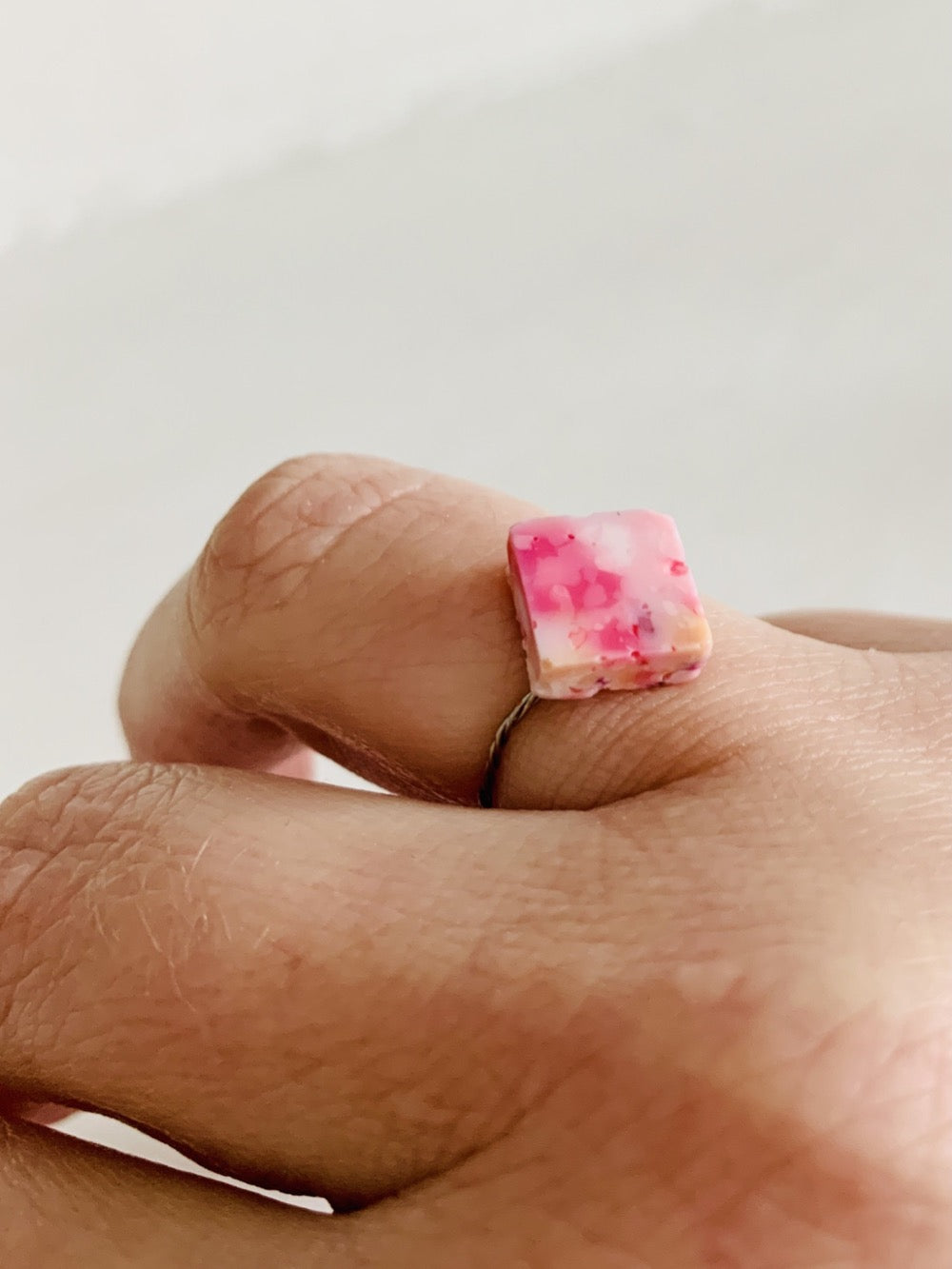 Shown on a person's ring finger and in front of a white background, there is a ring with a cast charm on a thin twisted band. The charm is cast from recycled 3D prints in shades of pinks, yellow, orange, and white. It has the look of granite or marble.