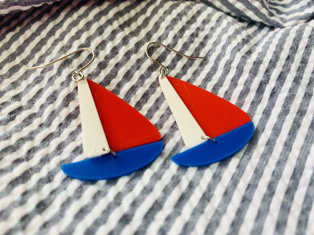 Two earrings are laying on seersucker fabric. The earrings are shaped like sailboats with a thin white sail, a bright red sail and a cobalt blue hull.