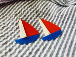 Load image into Gallery viewer, Two earrings are laying on seersucker fabric. The earrings are shaped like sailboats with a thin white sail, a bright red sail and a cobalt blue hull.