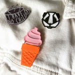 "Load image into Gallery viewer, Three plant-based 3D printed pins on a white denim jacked. One is shaped like a ice cream cone with a solid pink ice cream swirl above an orange sugar cone. Above these are a black and white geometric panda pin. There is also a tea cup shaped pin that shows as purple and a opaque white color. It has the words ""I have no chill"" written on it in the opaque white. In direct sunlight, this will turn bright hot pink."