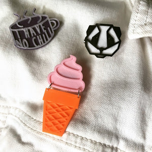 "Three plant-based 3D printed pins on a white denim jacked. One is shaped like a ice cream cone with a solid pink ice cream swirl above an orange sugar cone. Above these are a black and white geometric panda pin. There is also a tea cup shaped pin that shows as purple and a opaque white color. It has the words ""I have no chill"" written on it in the opaque white. In direct sunlight, this will turn bright hot pink."