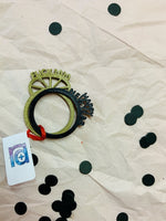 Load image into Gallery viewer, On a light pink paper tablecloth, black confetti is strewn and two 3D printed stacking rings are shown. The one in front is black and reads Happy New Year. It looks like the paper crowns people wear on New Years Eve. The second ring is gold. It reads, Fuck 2020.