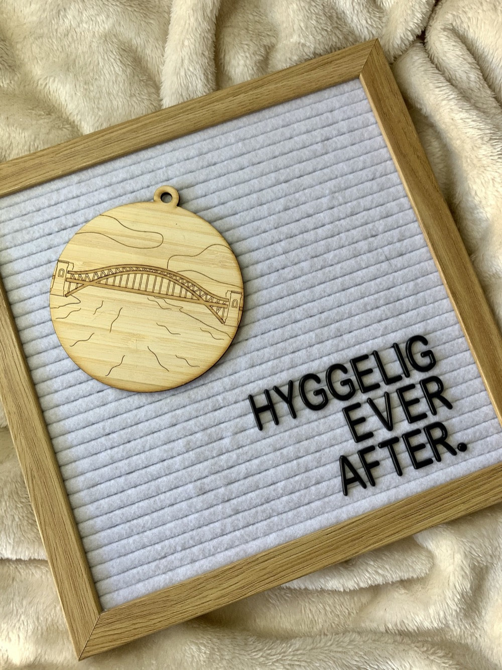 "Shown laying on a plush blanket is a letter board that reads ""Hyggelig ever after"". Also on the letter board is a laser cut wall hanging. It is cut from bamboo, a fast growing and sustainable grass. Etched in it a picture of the Hell Gate bridge in Astoria. This bridge is an icon of the area and looked on from Asttoria Park. This can be used as a ornament in the holidays or a wall hanging all year round. It can be painted like a paint by number or left plain."