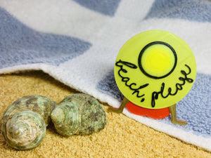 On the edge of a blue and white striped beach towel, next to sand and shells, is a 3D printed pin from R+D. The pin shows  someone wearing a red bathing suit and resting back on their hands. They are wearing a large, wide brimmed yellow hat that reads beach, please in a scripted black font.