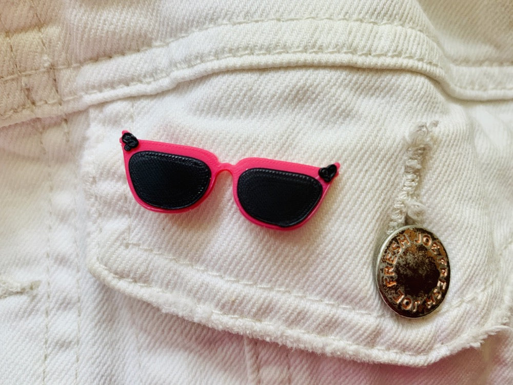There is a close up of a white demin jacket pocket. An R+D pin is attached that looks like a pair of cat eye sunglasses. They are hot pink with black frames and black accents in the corners.