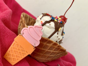 In the foreground is a sustainable ice cream pin that was 3D printed. The top of it is pink and looks like soft serve ice cream swirled into a peak. Below is an orange cone that looks like a classic sugar cone. In the background there is a waffle cone bowl holding an ice cream sundae with vanilla ice cream, rainbow sprinkles, chocolate sauce and topped with a bright red cherry.