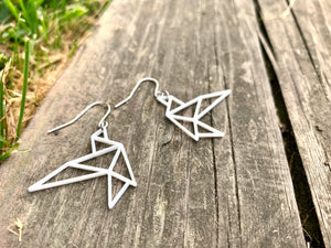 Laying on a old weathered piece of wood are two R+D earrings. They are shaped as geometric birds in flight. They are printed in a sustainable white filament that is plant based.