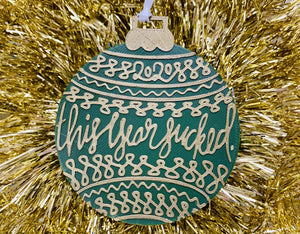 "On a background of bright gold tinsel garland is a R+D 3D printed ornament. The ornament is shaped like a traditional bulb. It is dark green with gold drawings and script on it. Worked into the doodles are the year 2020 and then the words, ""this year sucked""."