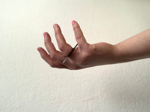 A hand is reaching into the frame across a white background. The hand is turned up like it may be recieving something. On the ring finger is a 3D printed ring that has a bar across the top. The bar is dipped in metallic paint on one side and extends over the middle and pinky fingers.