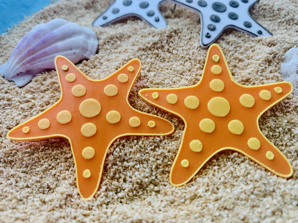 In the foreground are two R+D earrings. They are shaped like star fish and are orange with yellow outlines. There are yellow circles that stretch out on each leg of the starfish. They are laying on sand and shells and other star fish earrings are visible in the background.