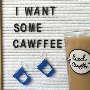 There is a white felt letter board with black letters reading, I want some cawffee and two earrings hanging below the words. The earrings look like classic Greek to-go coffee cups from New York City diners and bodegas. To the side of the letter board and earrings is a pint glass filled with milk and iced coffee from Fish's Eddy. It reads , Iced Cawffee in scripted lettering.