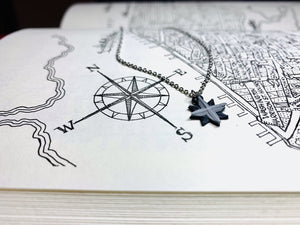 A book is opened to a drawn map of Manhattan, NY. Visable is the compass in the corner indicating North, East, South, and West. Laying next to the compass is an R+D necklace. The necklace is small and detailed. It is shaped like a compass and 3D printed in black and silver.