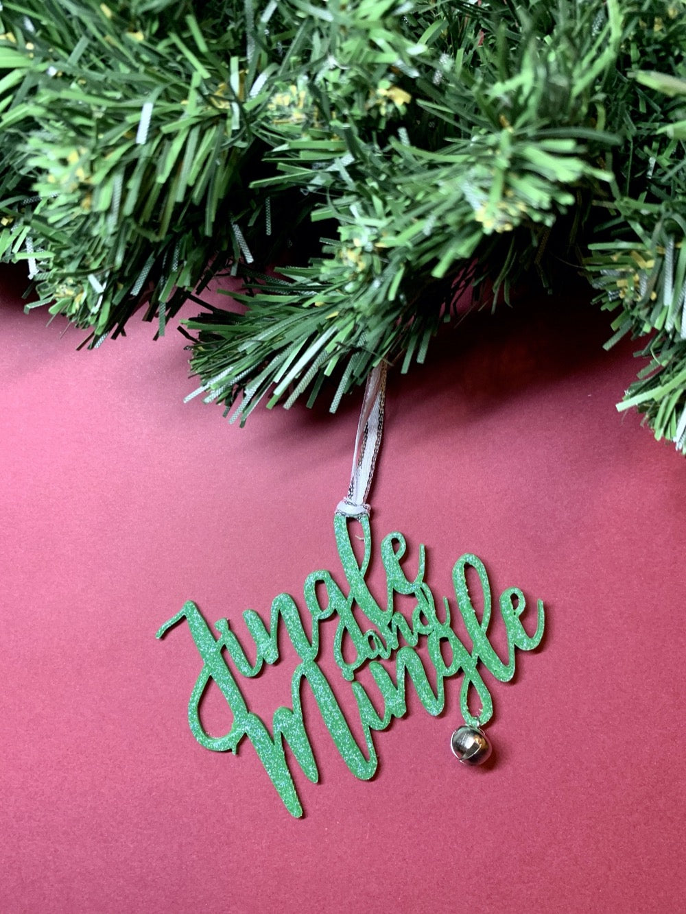 On a bright red background and hanging from a green wreath is a 3D printed R+D ornament. It is a cursive text with a jingle bell and covered in glitter to make it shimmer and shine in the light. This ornament reads, Jingle and Mingle.