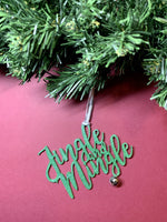Load image into Gallery viewer, On a bright red background and hanging from a green wreath is a 3D printed R+D ornament. It is a cursive text with a jingle bell and covered in glitter to make it shimmer and shine in the light. This ornament reads, Jingle and Mingle.