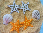 Load image into Gallery viewer, On a bed of sand are sea shells and two sets of earrings. The earrings are both shaped like star fish, with circles that are stretching out across each of the arms. One of the earring sets is gold and white, the other is orange and yellow.