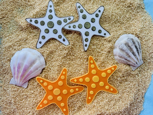 On a bed of sand are sea shells and two sets of earrings. The earrings are both shaped like star fish, with circles that are stretching out across each of the arms. One of the earring sets is gold and white, the other is orange and yellow.