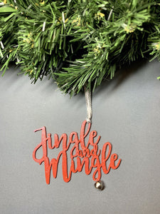 On a grey background and hanging from a green wreath is a 3D printed R+D ornament. It is a cursive text with a jingle bell and covered in glitter to make it shimmer and shine in the light. This ornament reads, Jingle and Mingle.