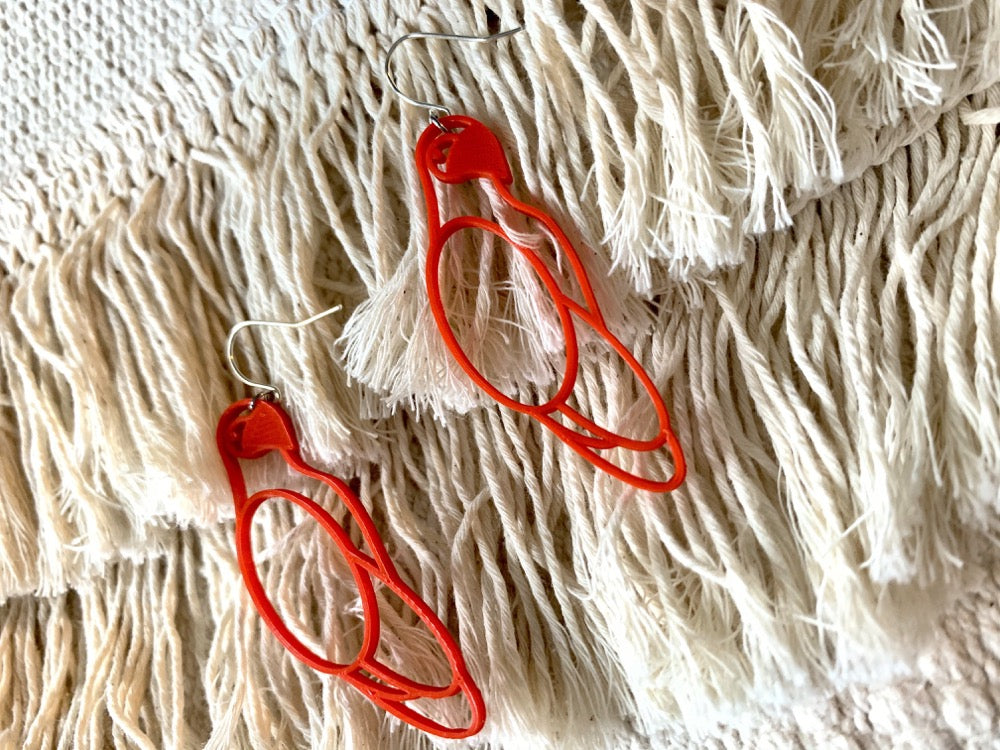 Two R+D earrings are laying on a background of cream tassels. The earrings are bright red and shaped like parrots.