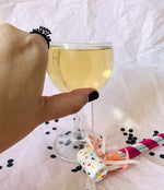 Load image into Gallery viewer, Reaching into the frame is a hand with a 3D printed ring on the pointer finger. It is a very small and delicate ring that reads Happy New Year. It looks like the paper crowns people wear on New Years Eve. The hand is reaching for a glass of champagne and a colorful noisemaker and black confetti are resting nearby.