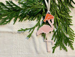Load image into Gallery viewer, On a white fabric background with sprigs of evergreen is a R+D 3D printed ornament. It is a light pink flamingo that has one leg up and is wearing a red santa hat.