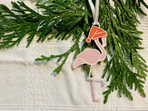 On a white fabric background with sprigs of evergreen is a R+D 3D printed ornament. It is a light pink flamingo that has one leg up and is wearing a red santa hat.