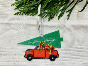 On a white fabric background with a branch of evergreens at the top there is a R+D 3D printed ornament hanging down. It is shaped as vintage style red car with a big green tree strapped on top. It is held together with red and green bows. The entire ornament is covered in glitter to be able to shimmer and shine in the light.