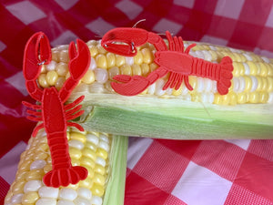 In the far background is a checkered white and red tablecloth from a classic picnic setting. In the foreground are two cobs of corn that are partially shucked. Resting on those cobs are two 3D printed earrings that are shaped like lobsters. They are bright red.