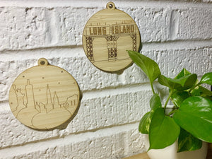 Shown on a white brick wall with a houseplant in the corner are two laser cut wall hangings. They are each cut from bamboo, a fast growing and sustainable grass. Etched on one is a picture of the Gantries in Long Island City, NYC. These gantries are an icon of the area and looked on from Manhattan and Gantry State Park. The other shows the nyc skyline with the statue of liberty, empire state building, Chrysler building and brooklyn bridge all visible.