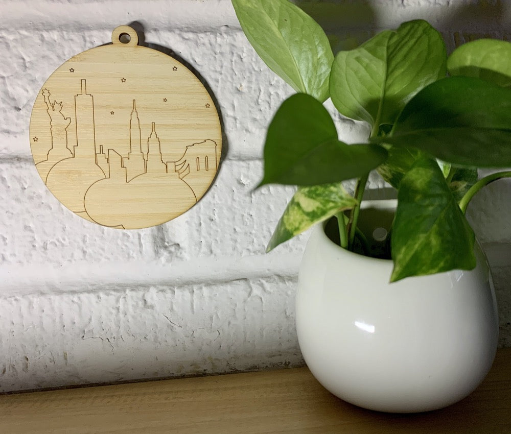 Shown on a white brick wall and next to a house plant is a laser cut wall hanging. It is cut from bamboo, a fast growing and sustainable grass. Etched in it a picture of the New York City Skyline with the Statue of Liberty, Empire State Building, Chrysler Building and Brooklyn Bridge all visible. Each piece can be painted like a paint by number or left plain. It can hang from your Christmas Tree or on you wall all year round.