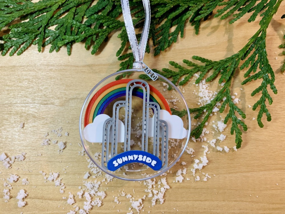 On a wooden shelf, there is a sprig of greenery and some scattered snow.Laying on top is a ornament with a small tag that has been 3D printed to read 2020. Inside the half circle ornament is a rainbow spanning between two clouds and the iconic Sunnyside Arch in front of it.