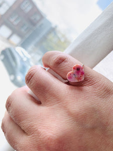A hand is pulling back a white curtain to reveal a bright outside. On their pinky finger there is a ring with a heart charm. The charm has a smooth surface and is cast from recycled 3D prints in pinks, oranges, reds, yellows, and whites.
