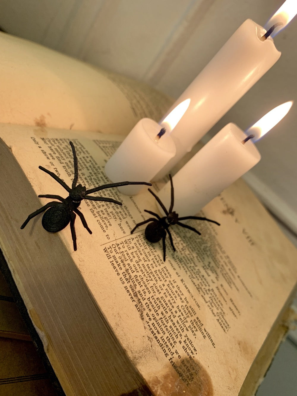 Shown are two spider earrings that are realistic in their shape. They are pictured crawling up an old book with lit candles on top to create a spooky Halloween scene.