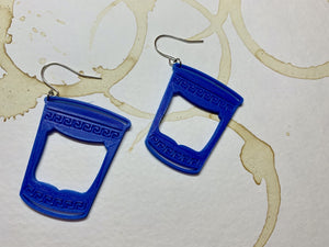 Two earrings that are made of a plant based plastic. They are in the shape of to-go coffee cups: The iconic ones from Greek diners or NYC bodegas with swirling borders and a big panel in the center. These earrings are resting on a paper that is stained with coffee rings overlapping one another.