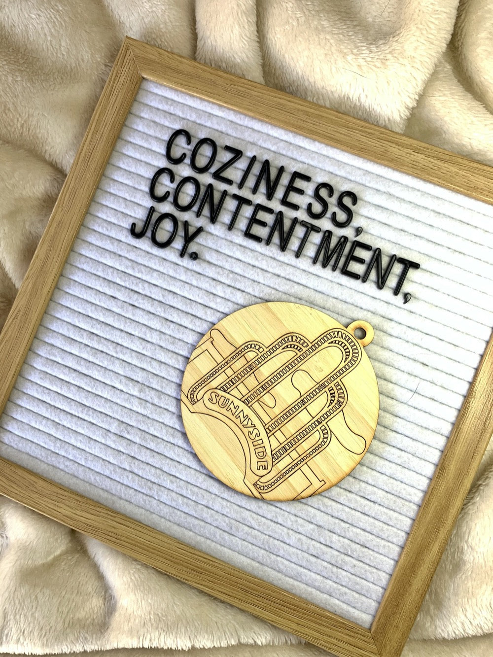 "Shown on a cozy blanket is a letter board that reads ""Coziness, Contentment, Joy."" There is also a laser cut wall hanging. It is cut from bamboo, a fast growing and sustainable grass. Etched in it a picture of the iconic Sunnyside Arch in the center of the Queens neighborhood. Each piece can be painted like a paint by number or left plain. It can hang from your Christmas Tree or on you wall all year round."