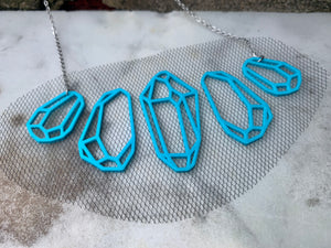 On a white marble background there is a R+D necklace. It is teal eco friendly filament in the shape of five crystals. They don't touch but are embedded with a black tulle fabric to stay together and look like they are floating when being worn.