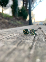 Load image into Gallery viewer, In focus are two R+D earrings shaped like leaves. They are olive green with gold veins. They are resting on weathered wood planks and there is a park blurry in the background.