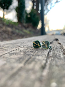 In focus are two R+D earrings shaped like leaves. They are olive green with gold veins. They are resting on weathered wood planks and there is a park blurry in the background.