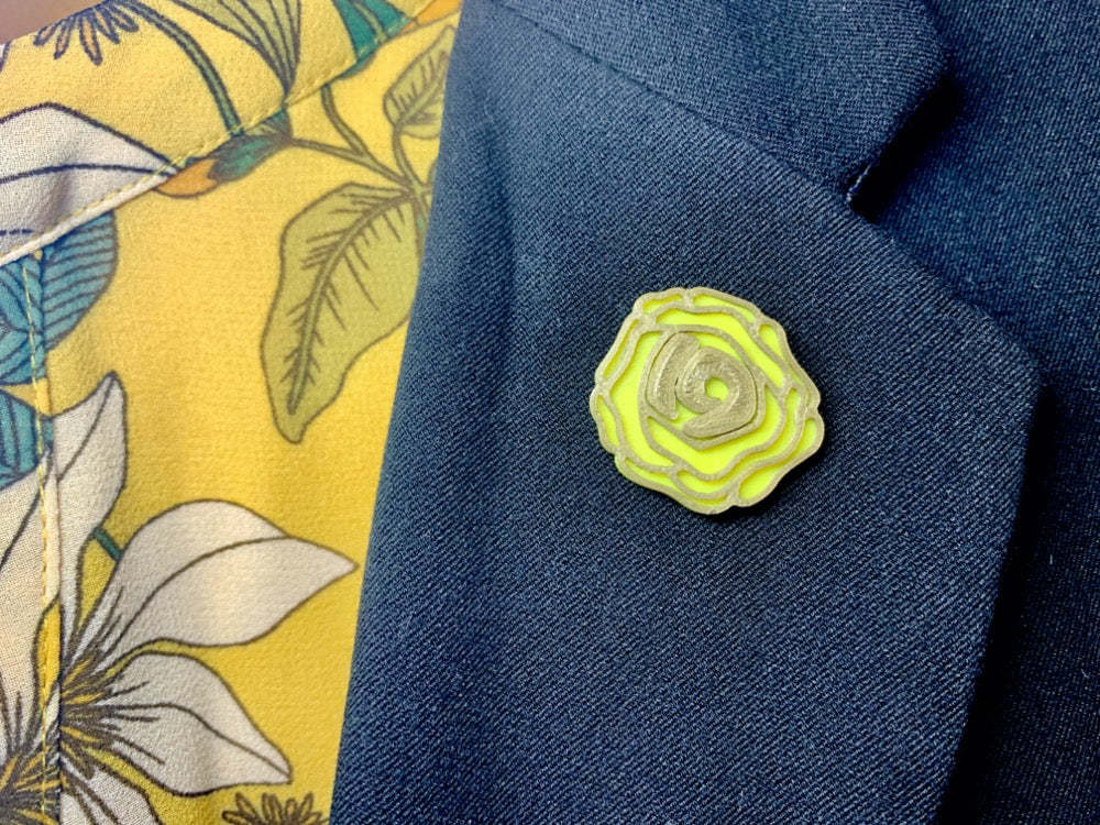 On a black suit lapel is a yellow rose pin. It's petals are outlined in gold and the center has the number 19. Those who were in support of the 19th amendment being ratified would wear a yellow rose.
