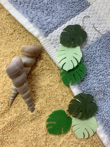 There are two earrings laying on a blue and white striped beach towel. They are small monster leaves that are layered together. The leaves are each different gradients of green: olive green, mint green, and kelly green. The towel is laying over bright fully sand with two twisted shells sitting nearby.