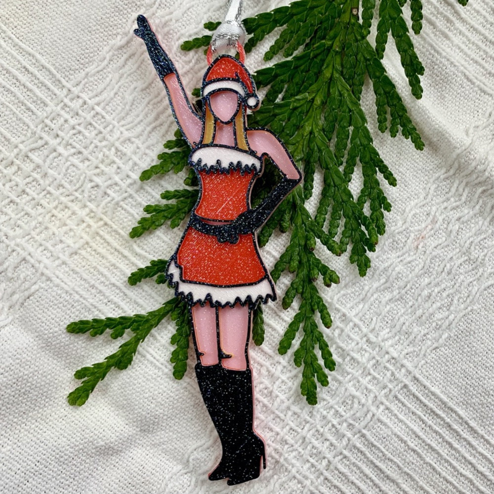 On a white fabric background there is a green branch from a tree. Laying on top of these is a 3D printed ornament from R+D. The ornament is printed in a plant based filament. It is shaped like Regina George from the movie Mean Girls. She is striking the iconic pose at the beginning of performing Jingle Bell Rock, wearing black gloves and boots and a red outfit with white trim.