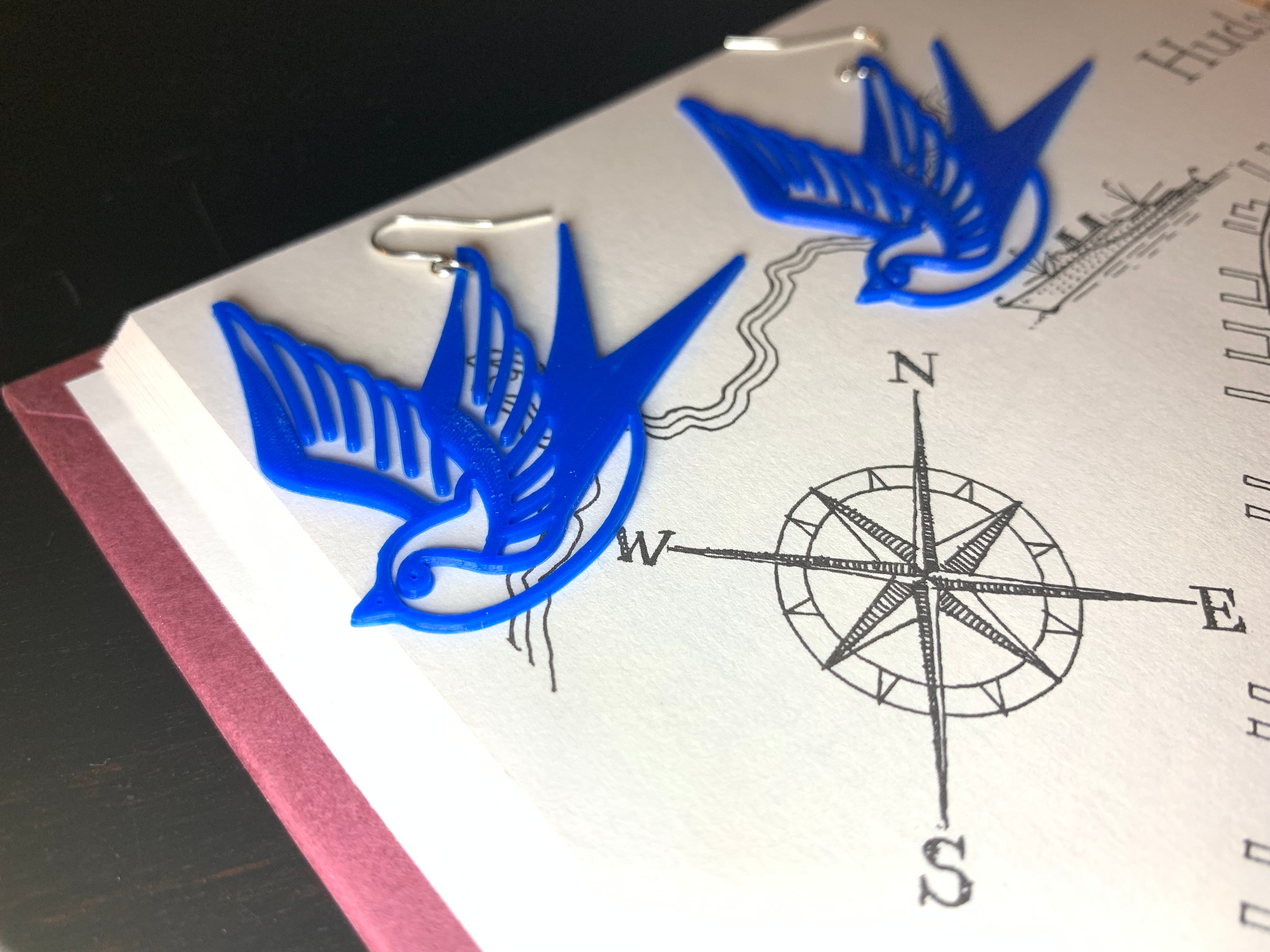 Laying on a book with a hand drawn compass are two bright cobalt blue swallow R+D 3D printed earrings. The shape of these birds is reminiscent of classic sailor tattoos.
